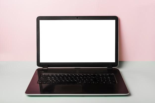 Primer del ordenador portátil con la pantalla blanca en el escritorio contra fondo rosado Foto gratis