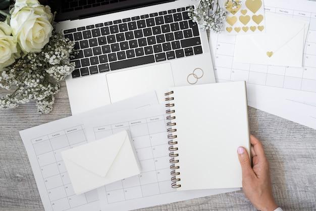 Primer de una persona que sostiene el cuaderno espiral en blanco con la computadora portátil; anillos de boda; flor; sobre y calendarios en escritorio de madera. Foto gratis