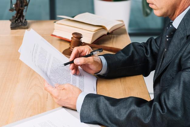 Primer plano, de, abogado de sexo masculino, tenencia, pluma, lectura, documento, en, escritorio de madera Foto gratis