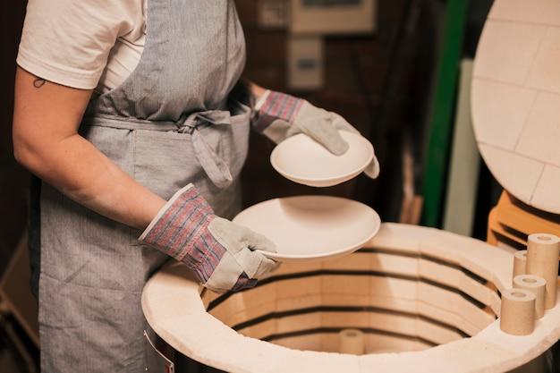 Primer plano del alfarero femenino arreglando las placas de cerámica. Foto gratis