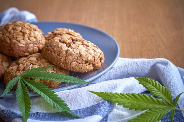 Primer plano de algunas galletas de avena en una placa gris sobre una toalla de rayas sobre una superficie de madera clara. Foto Premium