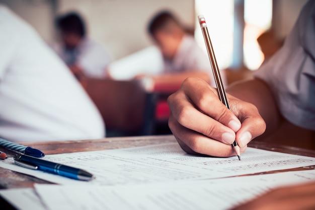 Primer plano del alumno con lápiz y escribiendo el examen final en la sala de examen o estudio en el aula. estilo vintage Foto Premium