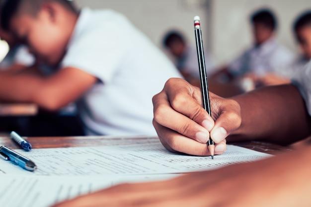 Primer plano del alumno sosteniendo el lápiz y escribiendo el examen final Foto Premium