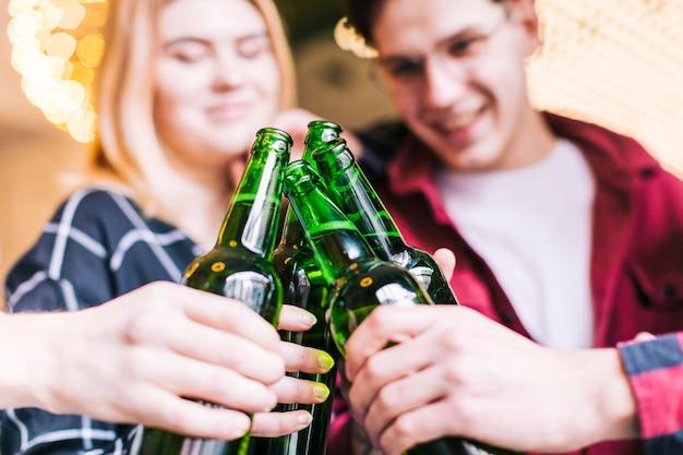 Primer plano de amigos brindando las botellas de cerveza verde Foto gratis