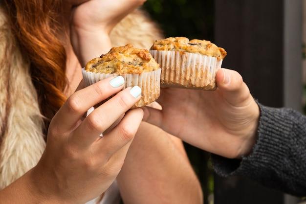 Primer plano de amigos con cupcakes Foto gratis