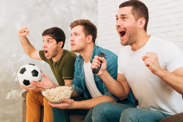 Primer plano de amigos viendo un partido de fútbol gritando y gritando Foto gratis