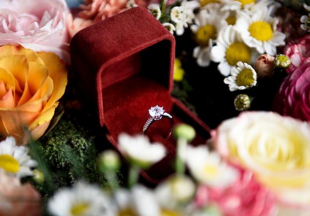Primer plano del anillo de bodas en caja roja con la decoración del arreglo de flores Foto gratis