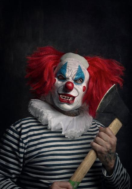 Primer plano de un aterrador payaso malvado con cabello rojo, ojos blancos, dientes ensangrentados, hacha en mano y una mirada amenazante Foto Premium
