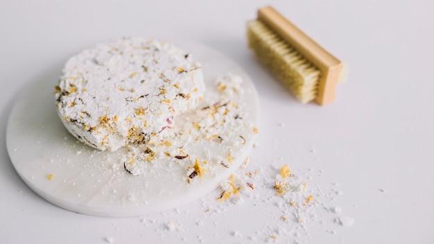 Primer plano de la barra de jabón roto y pincel sobre superficie blanca Foto gratis