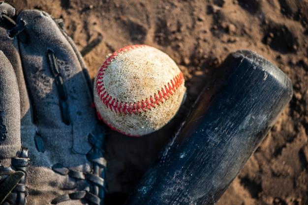 Primer plano de béisbol y bate en tierra Foto gratis