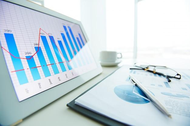 Primer plano de bolígrafo sobre informe económico con la ventana de fondo Foto gratis