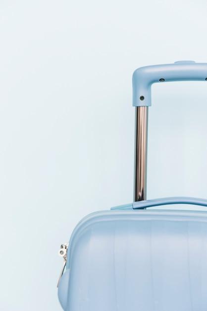Primer plano de una bolsa de equipaje de viaje de plástico sobre fondo azul Foto gratis