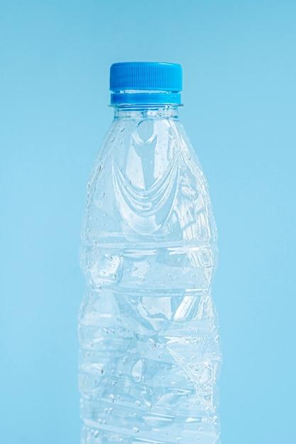 Primer plano de una botella de plástico sobre fondo azul. Foto gratis