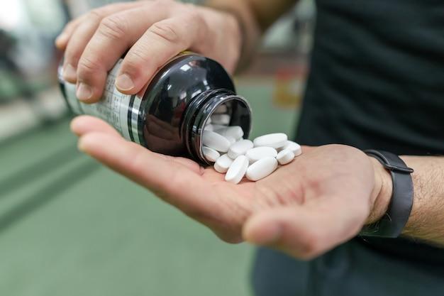 Primer plano de los brazos del hombre mostrando suplementos deportivos, cápsulas, píldoras Foto Premium