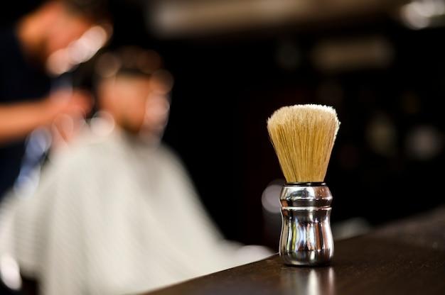 Primer plano de la brocha de afeitar con fondo borroso Foto gratis
