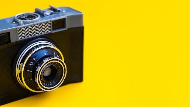 Primer plano de una cámara de fotos vintage con fondo amarillo Foto gratis