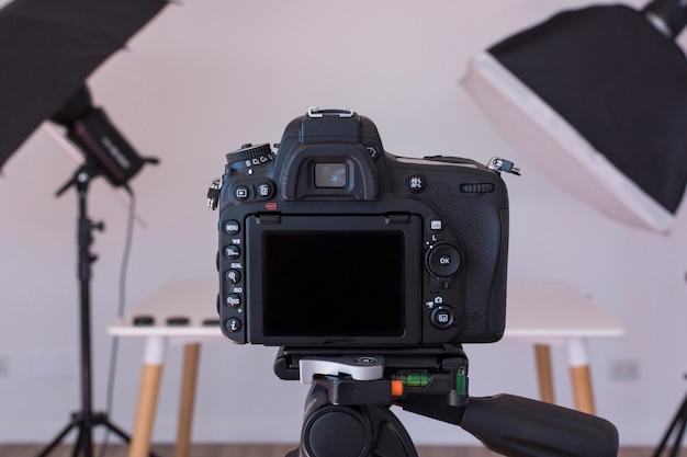 Primer plano de la cámara réflex digital en un trípode en estudio fotográfico Foto gratis