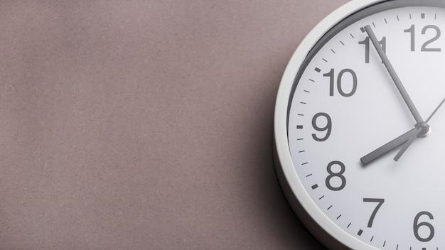 Primer plano de la cara del reloj contra el fondo gris Foto gratis