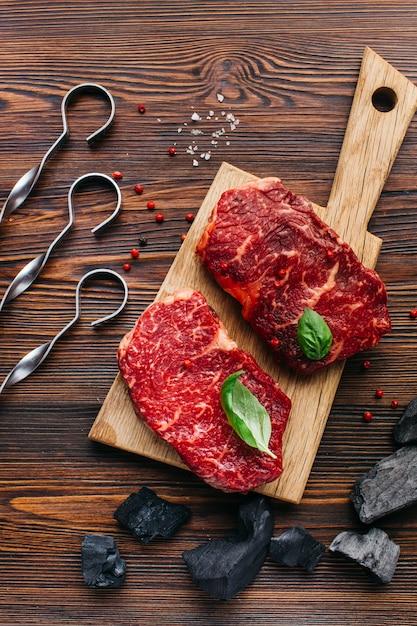 Primer plano de carne cruda con carbón y pincho metálico sobre fondo de madera Foto gratis