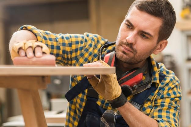 Primer plano de un carpintero macho frotando papel de arena en superficie de madera Foto gratis