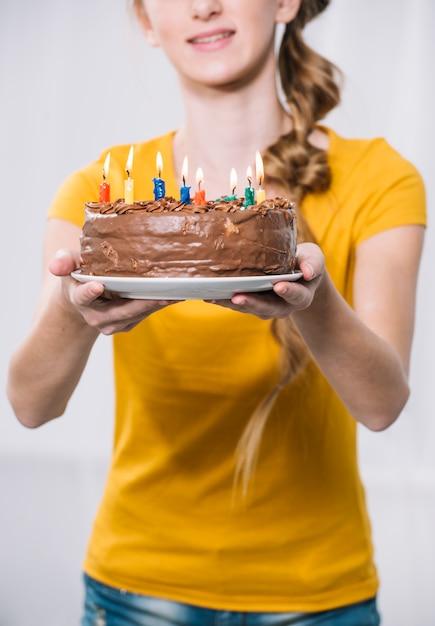 Primer plano de una chica con pastel de cumpleaños en un plato blanco sobre fondo blanco Foto gratis