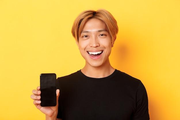 Primer plano de un chico coreano guapo con estilo mostrando la pantalla del teléfono inteligente y sonriendo complacido, recomendar la aplicación móvil, de pie sobre la pared amarilla Foto gratis