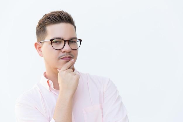 Primer plano de chico serio pensativo en gafas tocando la barbilla Foto gratis