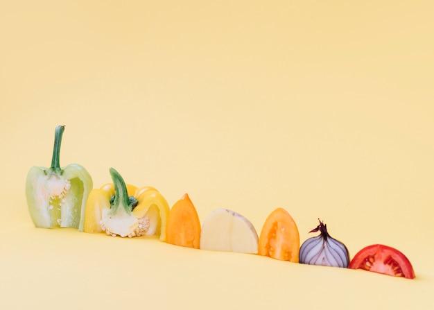 Primer plano de coloridas verduras crudas en superficie amarilla Foto gratis