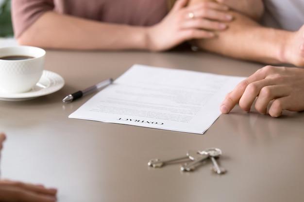Primer plano del contrato sobre la mesa, pareja tomando préstamo hipotecario Foto gratis