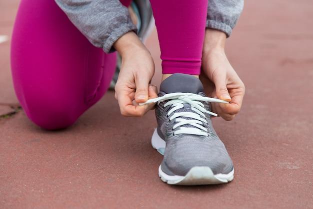 Primer plano del corredor que ata el cordón de zapato deportivo Foto gratis