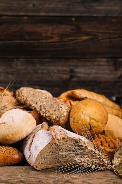 Primer plano de la cosecha de trigo frente a pan horneado en mesa de madera Foto gratis