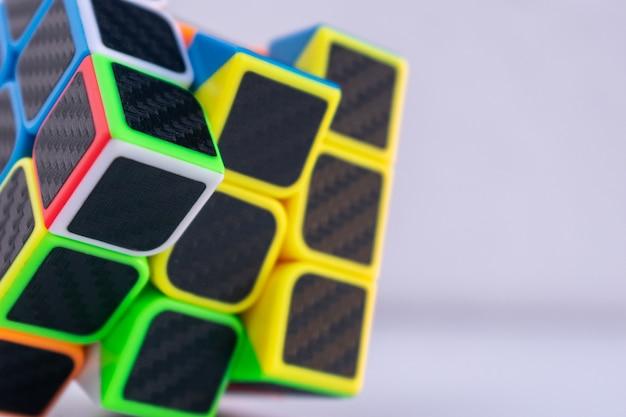 Primer plano de un cubo de rubik inacabado sobre una superficie blanca Foto gratis