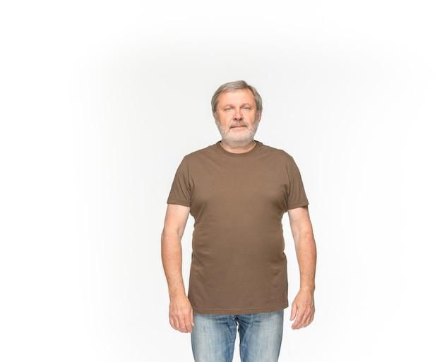 Primer plano del cuerpo del hombre mayor en camiseta marrón vacía aislado sobre fondo blanco. ropa, maqueta para el concepto de diseño con espacio de copia. vista frontal Foto gratis