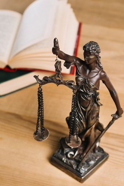 Primer plano de la dama de la justicia y los libros de derecho en el escritorio de madera Foto gratis