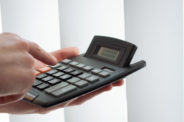 Primer plano de mano usando una calculadora Foto Gratis