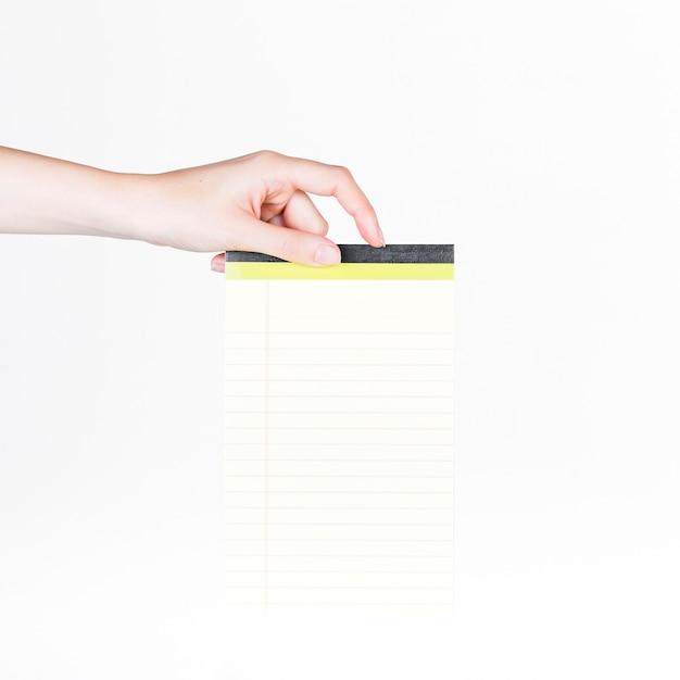 Primer plano de una mano humana con bloc de notas en blanco ...