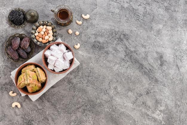 Primer plano de las delicias turcas tradicionales lukum y baklava con frutos secos sobre fondo gris de hormigón Foto gratis