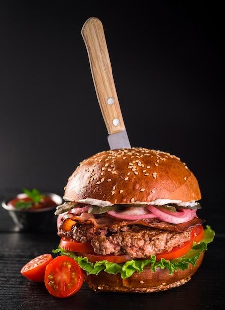 Primer plano deliciosa hamburguesa de ternera con tomates cherry Foto gratis