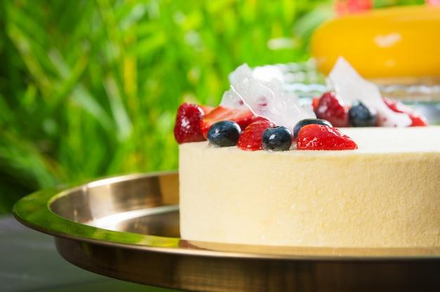 Primer plano de delicioso pastel de queso con bayas en bandeja al aire libre Foto gratis