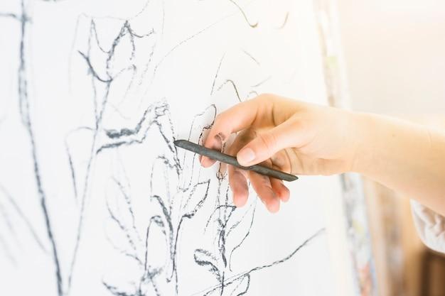 Primer plano del dibujo de la mano humana con carbón de leña Foto gratis