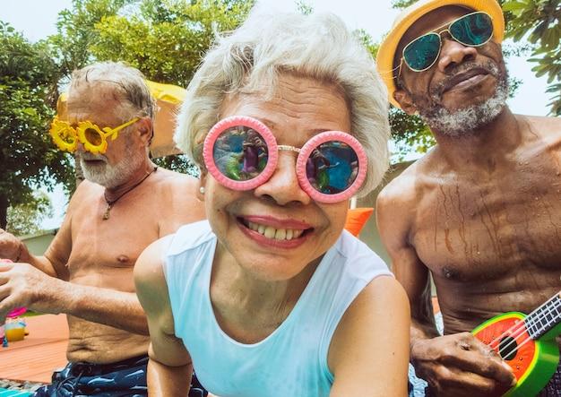 Primer plano de diversos adultos mayores sentados junto a la piscina disfrutando del verano juntos Foto gratis