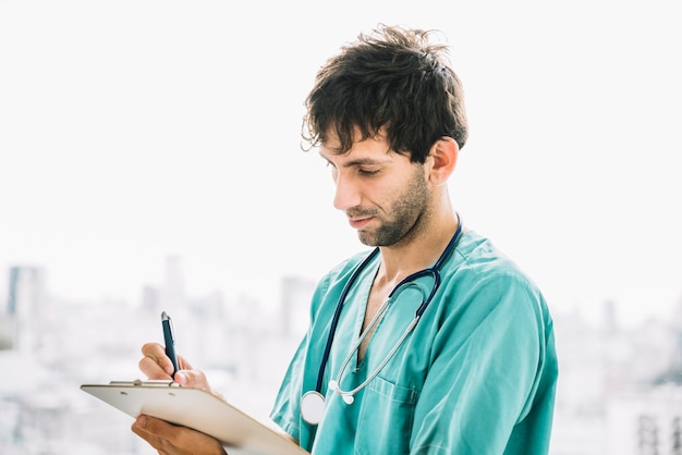 Primer plano de un doctor hombre escribiendo en portapapeles Foto gratis