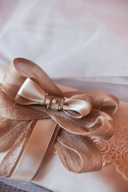 Primer plano de dos anillos de boda en una almohada roja Foto Premium