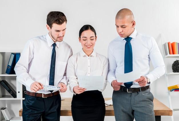 Primer plano de dos empresario y sonriente joven empresaria asiática mirando informe financiero Foto gratis