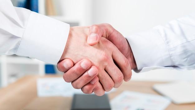 Primer plano, de, dos, hombre de negocios, sacudarir las manos Foto gratis