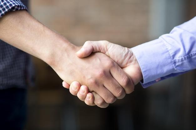 Primer plano de dos hombres de negocios estrechar la mano Foto gratis