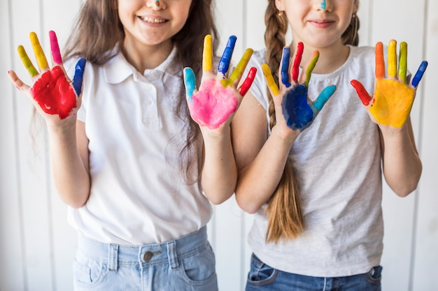 Primer plano de dos niñas sonrientes mostrando sus manos pintadas con color Foto gratis