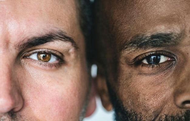 Primer plano de dos ojos de hombres étnicos diferentes Foto gratis