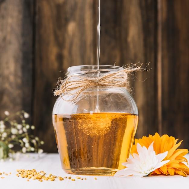 Primer plano de dulce miel goteando en frasco de vidrio con flores en el escritorio Foto gratis