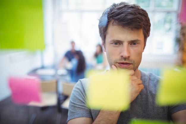 Primer plano de ejecutivo de sexo masculino de leer las notas adhesivas Foto gratis